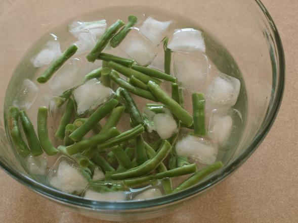 Flashing the blanched green beans in ice water
