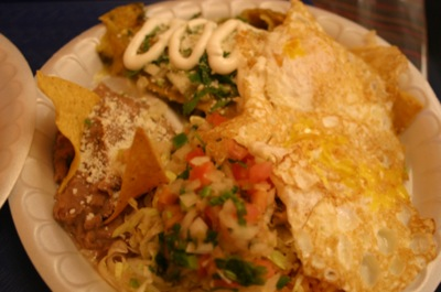 Chilaquiles and eggs with rice, beans and pico de gallo.