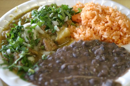 Guisado plate with puerco en salsa verde with refried black beans