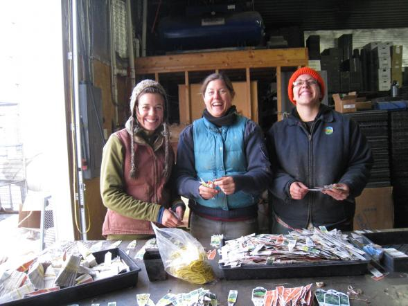 Molly, Ashley, and Beth stop to smile while sorting tags in the greenhouse